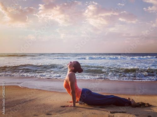 Foto op Aluminium Ontspanning Woman practices yoga asana Urdhva Mukha Svanasana at the beach