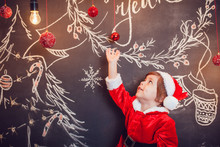Little Boy Dressed As Santa Claus Standing On Dark Background With Christmas Pattern. New Year.