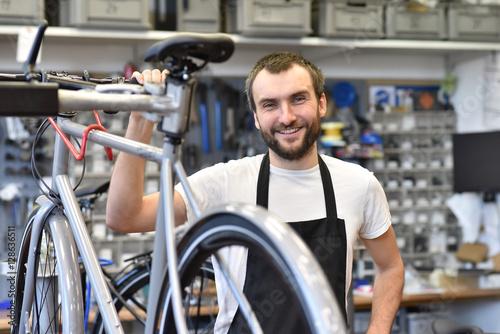 Poster Industrial geb. freundlicher Zweiradmechnaiker in einer Fahrradwerkstatt repariert Räder