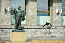 Young Man Jumping On Skateboard In Oslo Near By Statue Of Fat Man