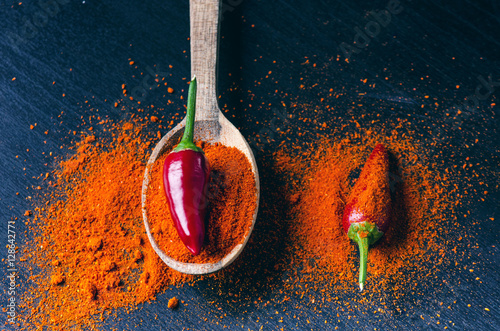 Fotografia  Red chilli peppers, spicy on a wooden spoon