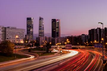 Obraz na płótnie Canvas Atardecer de Madrid con los rascacielos y las luces de la carretera