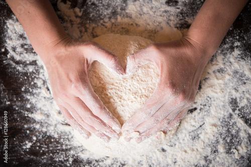 Fotografie, Obraz  Female hands holding dough in heart shape