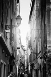 Fototapeta Uliczki - Beautiful view of scenic narrow alley street with historic traditional houses in an old town in Europe with blue sky and clouds in summer sunny day, with retro vintage black and white effect