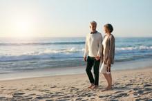 Loving Senior Couple Walking Along The Beach In Evening