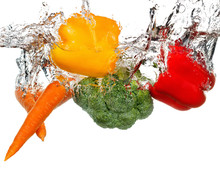 Vegetables In Water Splash. Isolated On White Background