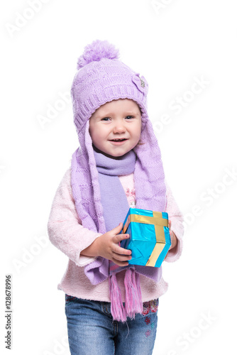 1d42b410bf8a Cute smiling little girl wearing violet knitted scarf and hat, holding  christmas gift isolated on white background. Winter clothes and christmas .