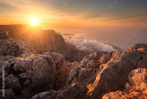 Cadres-photo bureau Lavende Mountain landscape at sunset. Amazing view from the mountain peak on rocks, low clouds, blue sky and sea in the evening. Colorful nature background. Adventure. Travel in Crimea. Beautiful scenery
