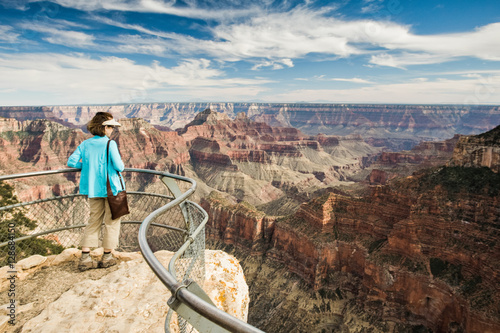 NORTH RIM GRAND CANYON, ARIZONA, USA. A woman in a teal sweater and cacky pants stands at a railing overlooking a deep desert canyon.