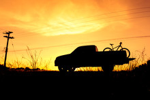 Silhouette Pickup Truck With Bicycle At Sunset Sky