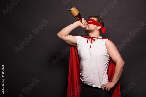 Tablou Canvas Super anti hero man drinking alcohol while posing in studio