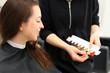 Koloryzacja włosów w salonie fryzjerskim. Fryzjerka doradza klientce kolor farby do włosów