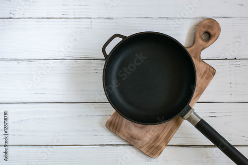 Fotografía  Old cast frying pan and cutting board are on the painted white wooden table