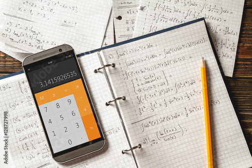 Mathematical equations written in a notebook. Calculator app.