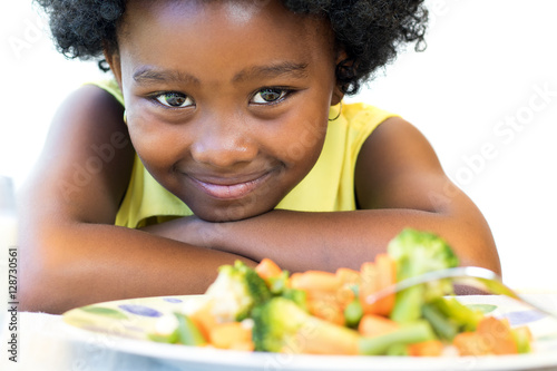 Deurstickers Kruidenierswinkel African girl in front of vegetable dish.