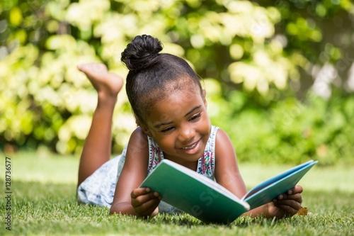 Fotografie, Obraz  Little girl reading a book at park