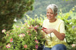 Mature woman cutting flowers with a pruner