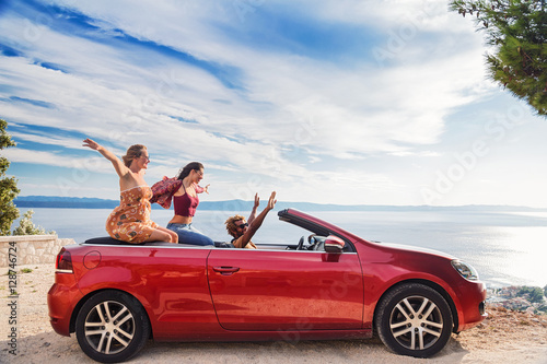Group of happy young people waving from the red convertible. - 128746724