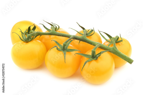 Photo  fresh yellow tasty tom tomatoes on the vine on a white background