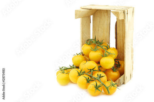 Photo  fresh dutch yellow tasty tom tomatoes on the vine in a wooden crate on a white