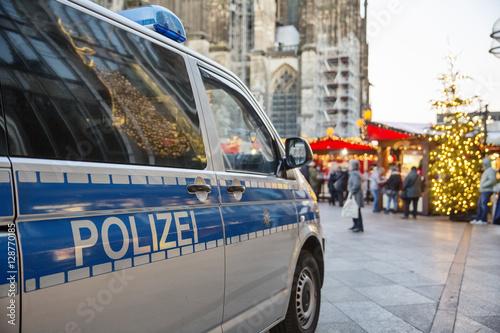 Fotomural  Einsatzwagen der Polizei parkt vor einem weihnachtsmarkt