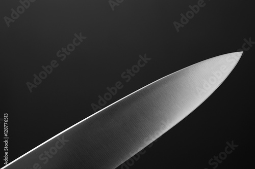 Fotografiet Big kitchen knife close up on dark background