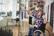 Businessman Assisting Handicap Colleague In Creative Office