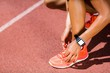 Female athlete tying her shoe laces on running track