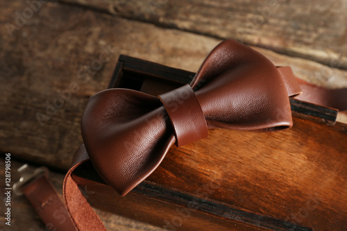Leather bow tie and gift box on wooden background Wallpaper Mural