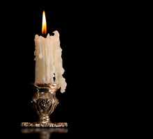 Burning Old Candle Vintage Bronze Silver Candlestick. Isolated Black Background.