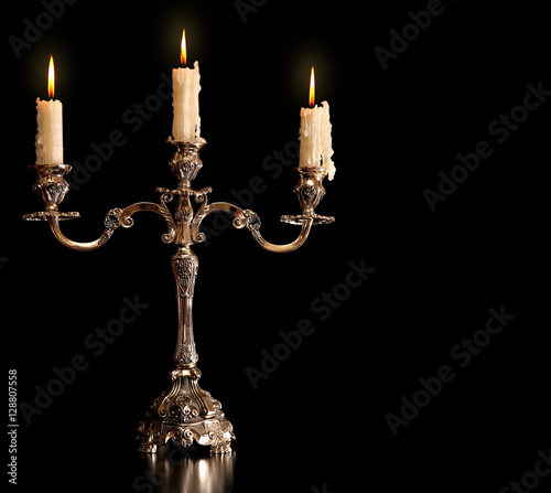 Photo burning old candle vintage bronze Silver candlestick