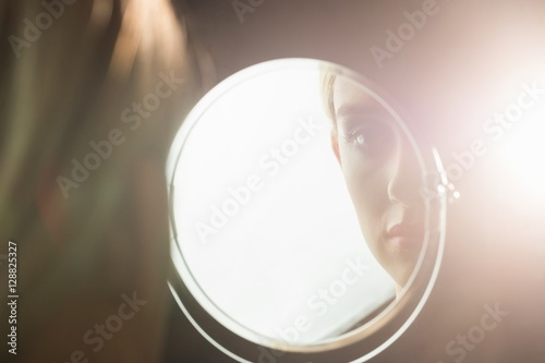 Portrait of a woman who is looking her in a mirror