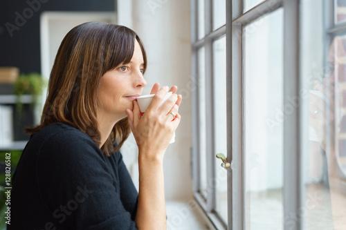 frau steht am fenster und trinkt einen kaffee