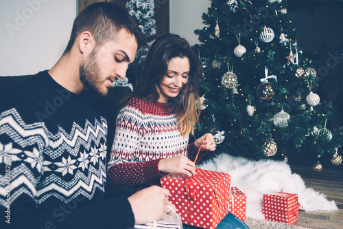 Couple unwrapping present Wallpaper Mural