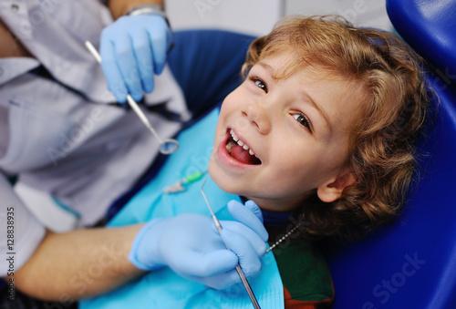 Fotografia  smiling child sitting in a blue chair dental