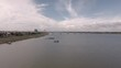 Aerial drone shot : low flying towards floating houses along the riverbank. Long bridge over a river in the background