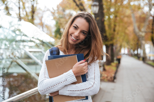 Photo  Smiling woman with notebooks standing in park