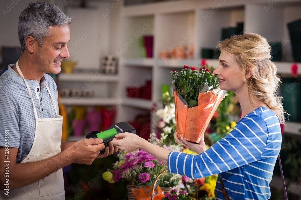 Fototapeta Woman making payment with her credit card to florist