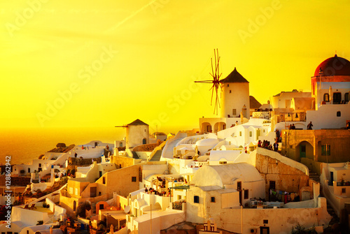 Poster Jaune famouse orange sunset of Oia with windmill, Santorini, retro toned