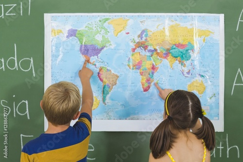 Plakat Dzieci w szkole, wskazując na mapie w klasie