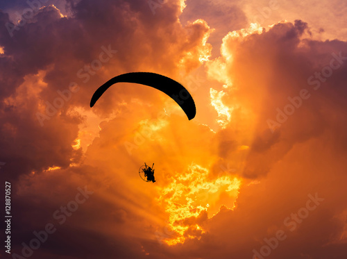 paraglider flying  with paramotor on sunset