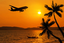Sunset On Tropical Beach And Coconut Palm Tree And Fisherman Boat With Silhouette Airplane Flying Over The Sea In Thailand