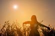 Silhouette of happy women open hand in grass field at the sky su
