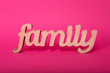Leinwandbild Motiv Word family, wooden letters on pink paper background. Love and unity concept.