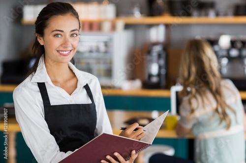 Cuadros en Lienzo Portrait of smiling waitress writing in a file
