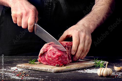 Fotomural Man cutting raw beef meat