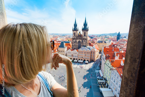 Acrylic Prints Prague Kostel Panny Marie pred Tynem. Church of the Virgin Mary. A young woman stands on top of the clock tower and looks at the Old Town Square in Prague