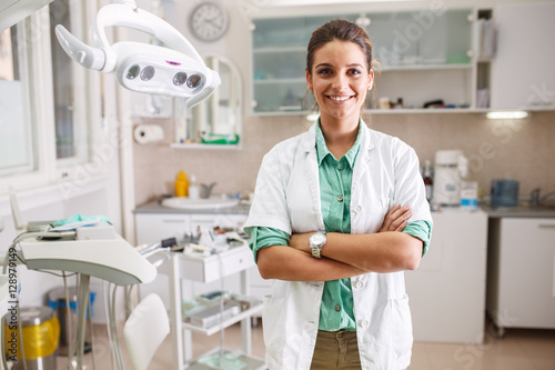 Portrait of  female dentist .She standing in her dentist office.