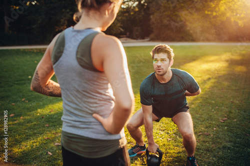 Photo Personal trainer with man doing weight training in park
