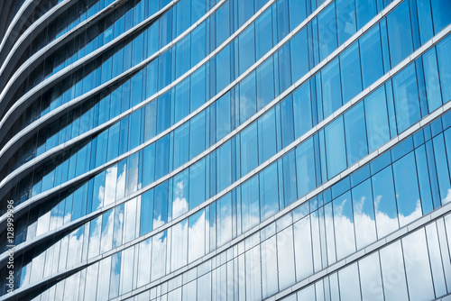Pattern of blue glasses in high building with shadow of cloud. A